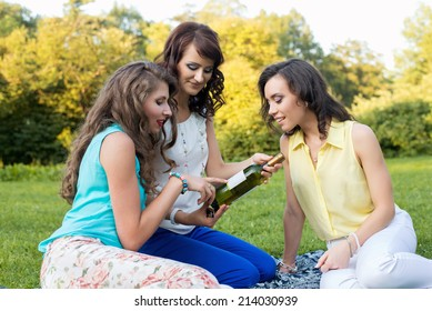 Three young pretty girlfriends opening a bottle of wine on the meadow during the picnic, smiling and having fun.
