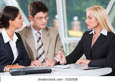 Three young professionals gathered together discussing important business plan in the cafe
