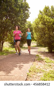 Three young runners on a paved jogging trail in daylight surrounded by trees and bushes in the late morning wearing t-shirts and black pants