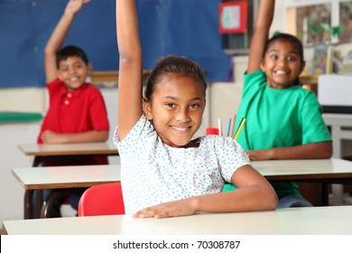 Three young school children arms raised in class