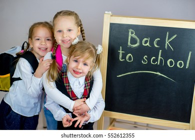 three young schoolgirls near the blackboard with schoolbag. isolated on white background