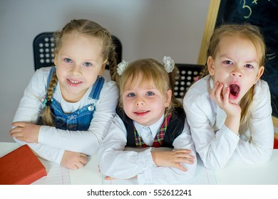three young schoolgirls sitting at the table. isolated on white background