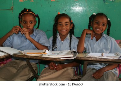 Three young schoolgirls sitting together in the classroom