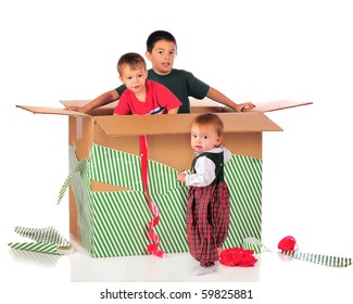 Three young siblings playing in the box of a giant Christmas gift.  Isolated on white.