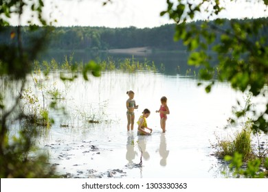 Three young sisters taking healing mud baths on lake Gela near Vilnius, Lithuania. Children having fun with mud. Kids playing with medicinal clay.