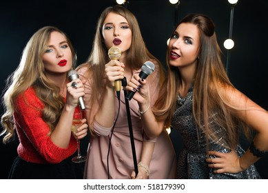 three young smiley beautiful long hair women with microphones singing songs on the stage in karaoke