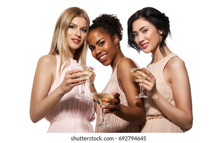 Three young smiling women: European, African American and Asian girls celebrate a bachelorette party in evening beige dresses, holding glasses with champagne.