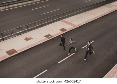 Three young sportspeople running the street