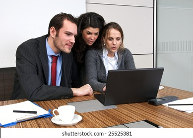 Three young staff members discussing business matters in a  modern office cubicle, whilst browsing a laptop