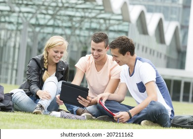 Three young student laugh about something on their Ipad
