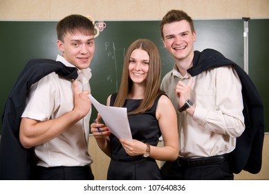 Three young succeeding the businessman against a board. All smile