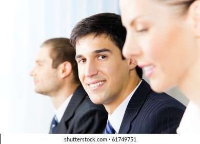 Three young successful businesspeople at office, with selective focus on man