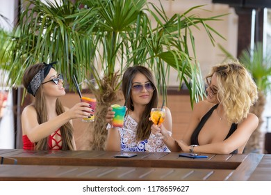 Three young woman with a glass of cocktail,having fun