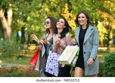 three young woman with shopping bags in a park in autumn