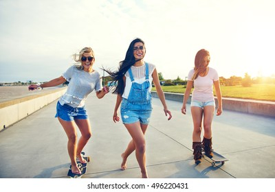 Three young woman skateboarding at the beach along a deserted waterfront promenade laughing and smiling backlit by the morning sun