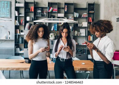 three young women business team indoor using smart phone - remote working, phubbing, business concept