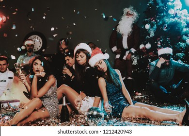 Three Young Women Celebrating New Year on Party. Santa Claus Cap. People in Red Caps. Happy New Year Concept. Glass of Champagne. Celebrating of New Year Concept. Young Woman in Dress.