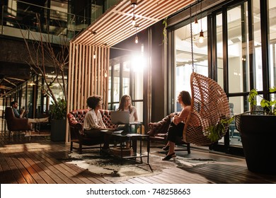 Three young women discussing new business ideas while sitting on creative office. Modern office lobby with business people doing meeting.