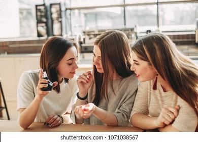 Three young women friends smelling new perfume. Shopping, sale, cosmetics, perfumery, friendship, women
