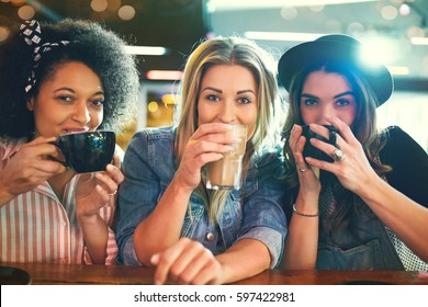 Three young women front portrait close-up at cafe table sipping coffee from their cups, looking at camera and smiling