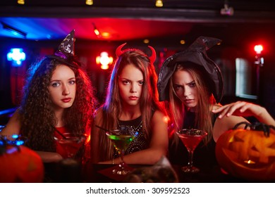 Three young women in Halloween hats in nightclub