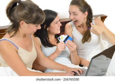 Three young women having fun and making shopping on-line