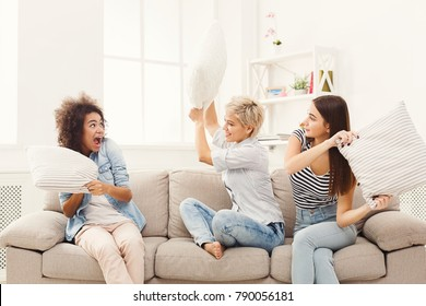 Three young women having pillow fight sitting on sofa at home. Female friendship, leisure, entertainment and fun, copy space