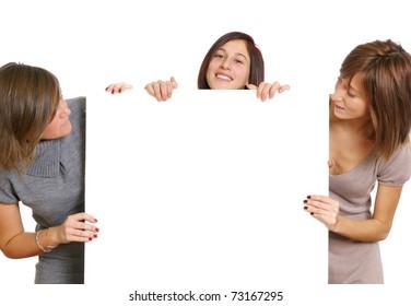 Three young women holding blank billboard