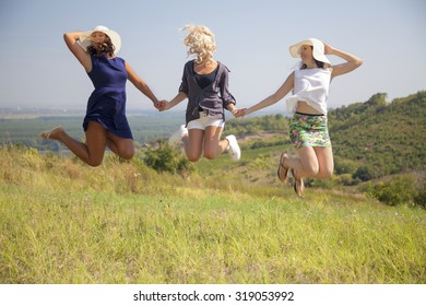 Three young women jumping high in the air on the grass. Girls holding hands and having fun in nature.