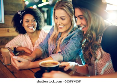 Three young women laughing and joking together as they look at something on the screen of a mobile phone while meeting for coffee at a cafe