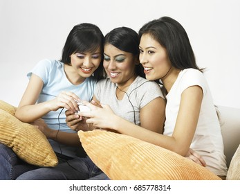 Three young women listening to MP3 player, smiling