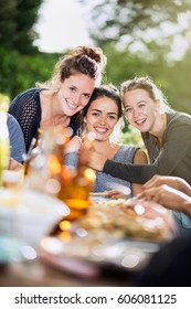Three young women lunching on a terrace with friends pose for a photo. Shot with flare
