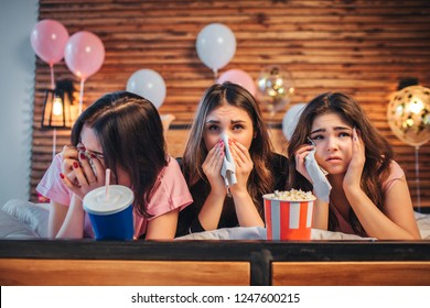 Three young women lying on bed in festive room. They watch movie and cry. Girls hold white napkins in hands.