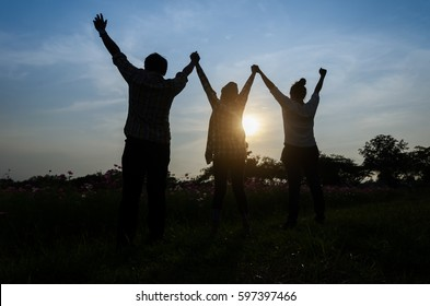 Three young women and men raise hands up in the air for the victory, teamwork concept