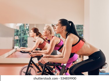 three Young women on exercise bikes at gym