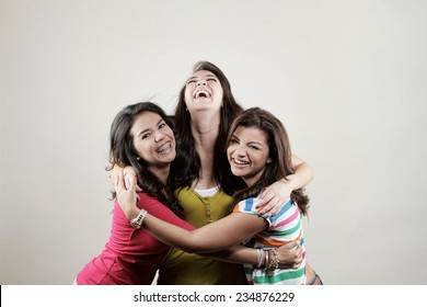Three young women posing in the studio smiling as best friends