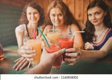 three young women sit in cafes and pizza, chat, laugh, eat pizza and drink juice. Girls are minted by glasses or glasses with drinks. A hen party with friends