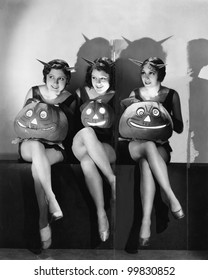 Three young women sitting and holding Jack O' Lanterns on their laps