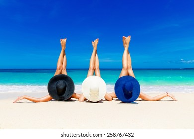 Three young women in straw hats lying on a tropical beach, stretching up slender legs. Blue sea in the background. Summer vacation concept.