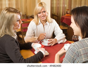 Three young women talking at the cafe table