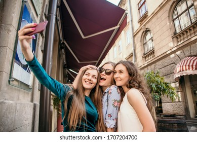 Three young women are walking in the city and having fun. Summer mood