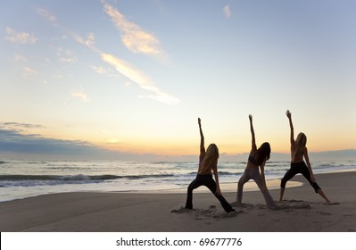 Three young women in a warrior position practicing yoga on a beach at sunrise or sunset