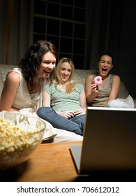 Three young women watching a movie