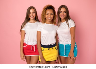 Three young women in white t-shirts and bright sports skirts.