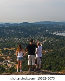 Three  youths look out over the Saanich Peninsula north of Victoria on Vancouver Island, BC Canada