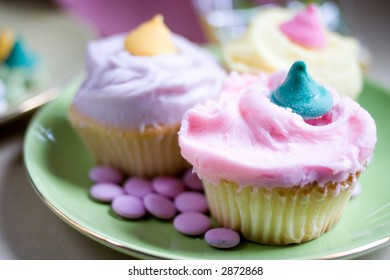 three yummy Easter pastel cupcakes on a green plate with lilac pastilles