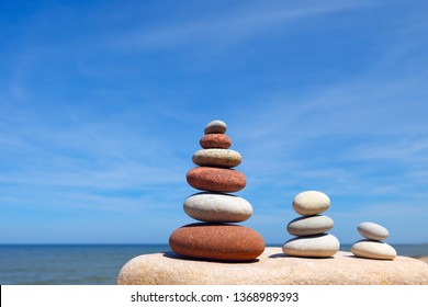 Three Zen pyramid of balanced stones on a background of the summer sea and blue sky. Concept of spiritual harmony, balance and meditation