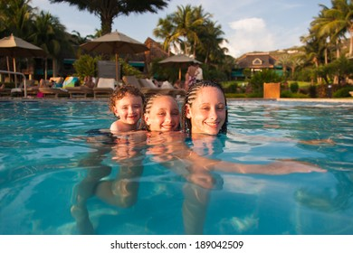 Three,children playing piggyback while swimming in a pool in Cruz Bay, St. John, USVI