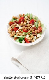 Three-fourths angle of BLT pasta salad with crispy bacon, grape tomatoes, green leafy lettuce and fresh mozzarella in white bowl with beige linen.