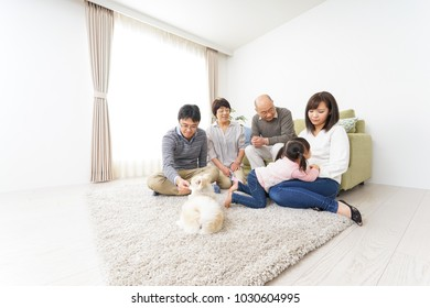 Three-generation family playing with dog